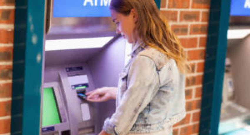 Woman using an ATM after checking for skimming device