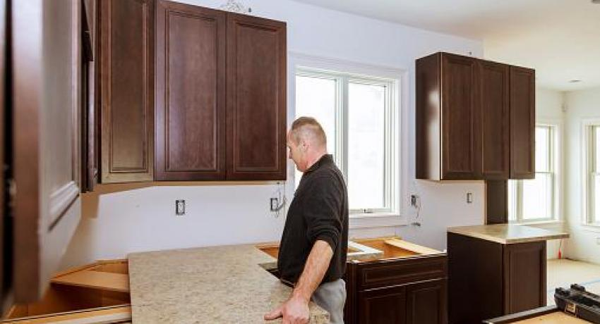 Man installing countertop in kitchen